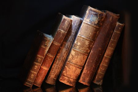 Old books in a row isolated on dark background