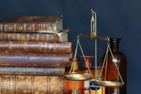 quinine: Vintage weight scale on background with old books and vials