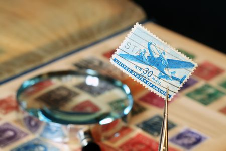 philately: Close-up of pincers with old USA postage stamp on background with philately collection