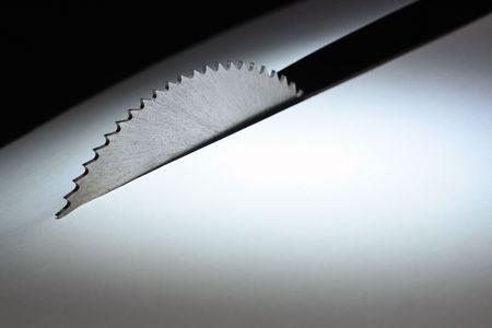 saw blade: Circular saw cutting white paper sheet on dark background