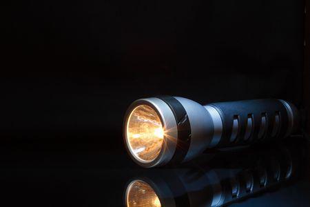 blackout: Modern flashlight with orange beam isolated on dark background