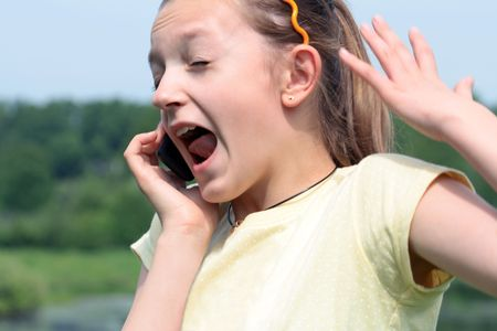 Close-up of nice young girl crying with mobile phone on nature background photo