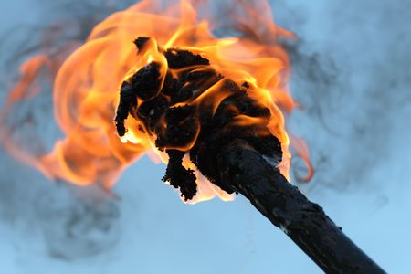 Closeup of flaming torch with fire and black smoke on blue background