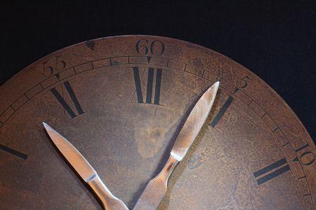 scalpels: Closeup of old rusty bronze clock dial. Clock hands made from sharpen steel scalpels