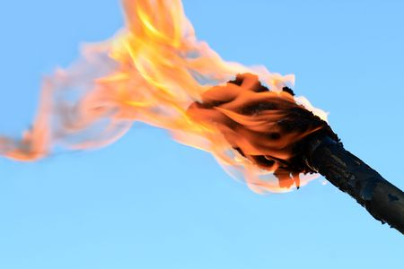 Closeup of flaming torch on blue background with copy space