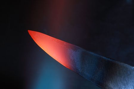 farriery: Abstract dark background with closeup of red-hot knife in flame