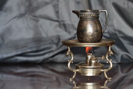primus: Ancient bass jug standing on vintage table spirit lamp with fire