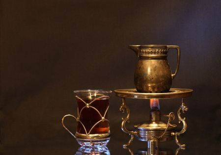 primus: Cup of tea near ancient brass jug standing on vintage table spirit lamp with flame Stock Photo