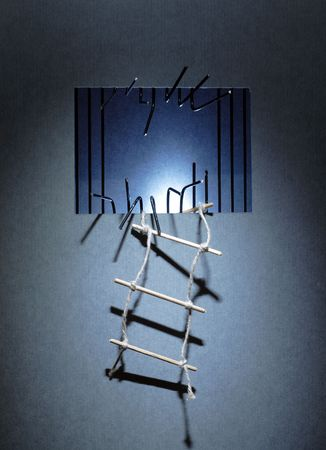 Rope ladder hanging on the prison wall with sawed metal bars