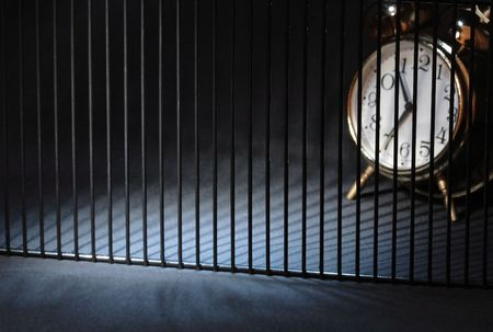 Alarm clock behind bars on dark background with copy space Stock Photo - 5618252