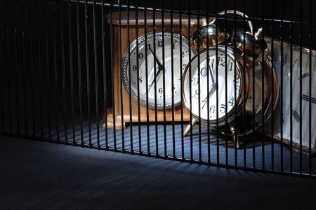 Three alarm clocks behind bars on dark background with copy space Stock Photo - 5618253