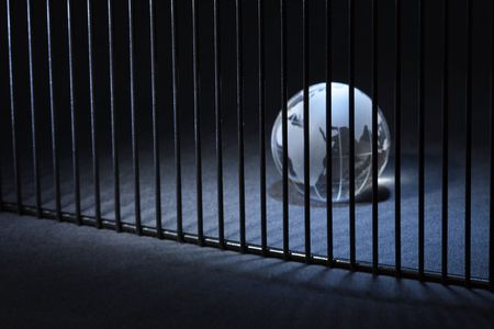 behind bars: Glass globe behind bars on dark background with copy space