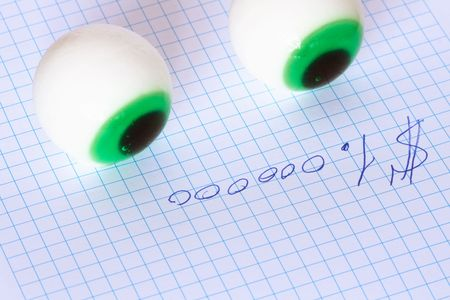 million dollars: Two toy eyes lying on paper with inscription One million dollars