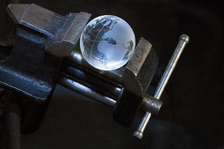vise grip: Glass globe inside old vise grip on dark background
