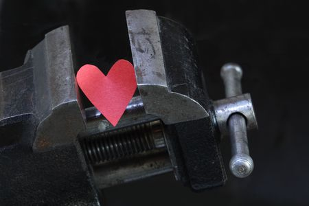 Small red paper heart under pressure with old vise grip on dark background photo