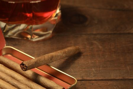 Metal box of cigars and glass of whiskey on wooden background photo