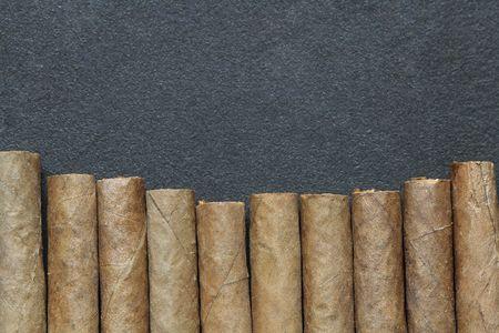 cuban culture: Closeup of cigars row on dark metal background