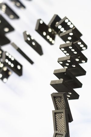 topple: A stack of black dominoes falling on white background Stock Photo