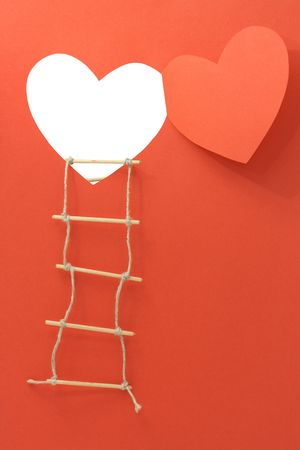 windows frame: Rope ladder hanging on the wall with open window like a heart made from red paper.  Stock Photo