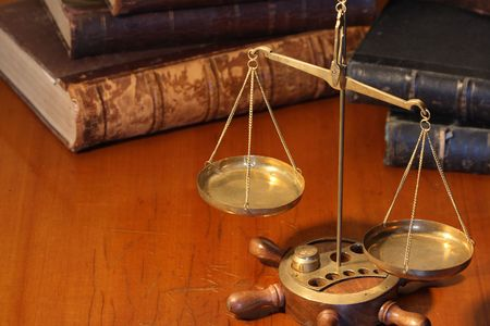 justice scales: Ancient weight scale standing on wooden table near old books Stock Photo