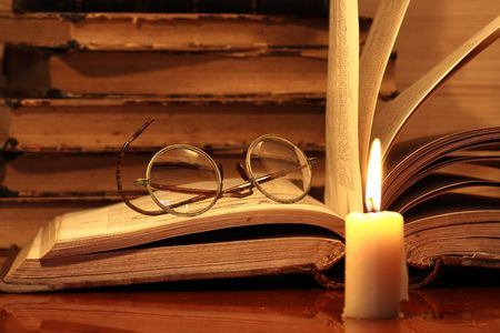 Closeup of candle with burning flame on background with old books and spectacles photo