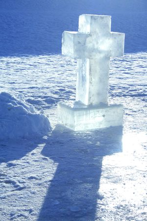 Cross made from ice standing on snow background photo