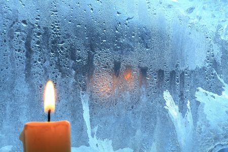 Candle with burning flame on background with frozen wet window photo