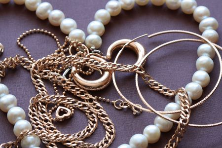 Closeup of various gold and pearl jewelry on brown textiles background Stock Photo - 6339428