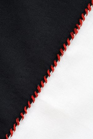 seam: Closeup of black and white textile material jointed by red thread seam Stock Photo