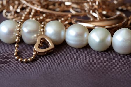 Closeup of various gold and pearl jewelry on brown textiles background Stock Photo - 6339457
