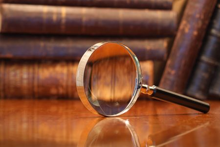Still life with magnifying glass standing on wooden table on background with old books Stock Photo