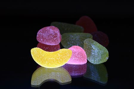 reverberation: Lot of multicolored fruit jelly with reverberation on black background Stock Photo