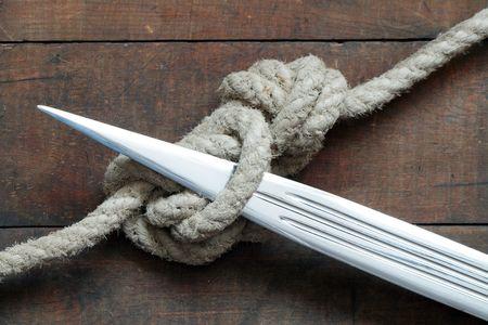 Closeup Dolk en kabel knoop gebonden op houten achtergrond Stockfoto - 6507847