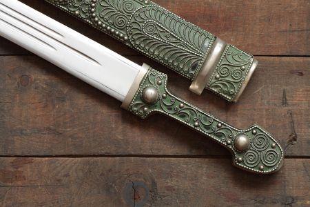scabbard: Detalle de antig�edad daga cauc�sicos y vaina sobre fondo de madera