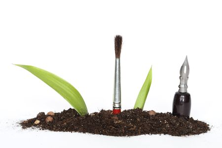 Green leaves, pen and paintbrush inside growing out of earth on white background  Stock Photo - 6507885