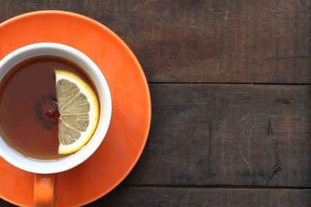 Cup of hot black tea with lemon on wooden background with copy space Stock Photo