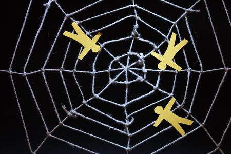 Conceptual background with web made from rope and yellow paper men on dark photo