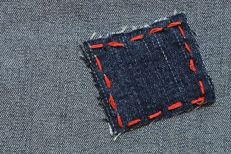 sewing item: Patch with red thread attached on jeans textured