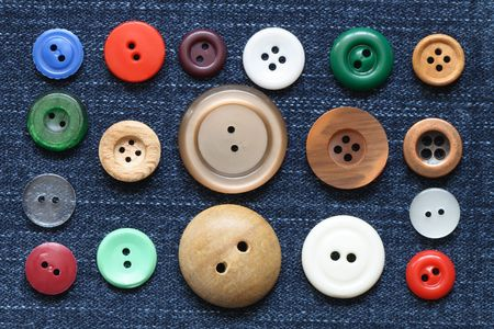 Set of various buttons lying on jeans textured background photo