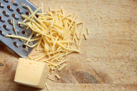 queso rayado: Detalle de queso rallado y rallador acostado en la tabla de cortar madera