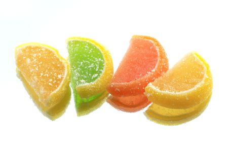 reverberation: Few colored fruit jelly lying in a row on glass background with reverberation