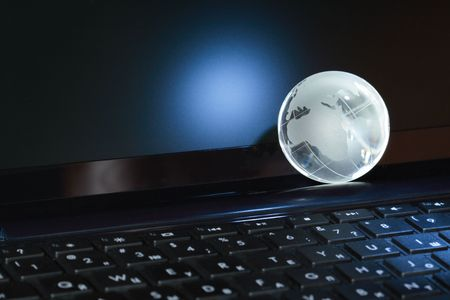 Closeup of glass globe lying on black computer keyboard photo