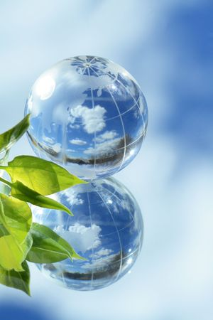 reverberation: Closeup of glass globe and green leaves lying on mirror background with blue sky and clouds reverberation Stock Photo
