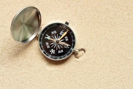 Closeup of open compass lying on yellow sand background with copy space photo