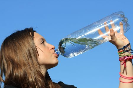 Beauty teenage girl drinking water against the blue sky photo