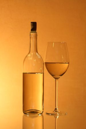 reverberation: Wineglass near bottle of white wine with reverberation on red-yellow background