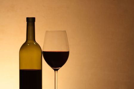 reverberation: Wineglass near bottle of red wine with reverberation on brown background