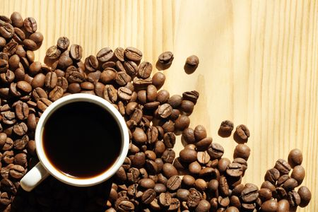 Cup of black coffee and coffee beans on wooden background