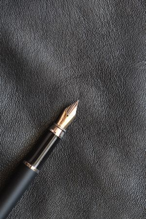 Fountain pen lying on black leather background with copy space photo