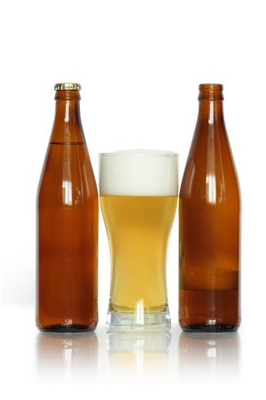 near beer: Glass of lager beer near two bottles